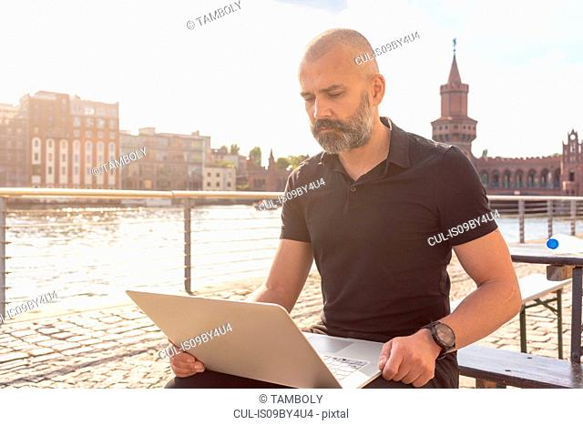 Man using laptop on bridge, river, Oberbaum bridge and buildings in background, Berlin, Germany