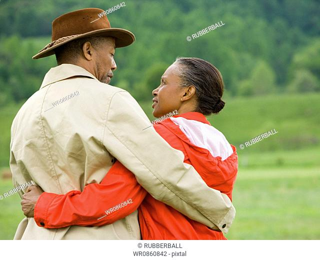 Rear view of a senior man and a senior woman with their arms around each other