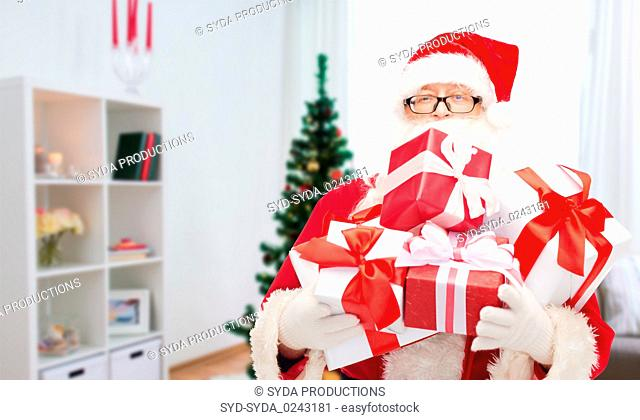 santa claus with christmas gifts at home