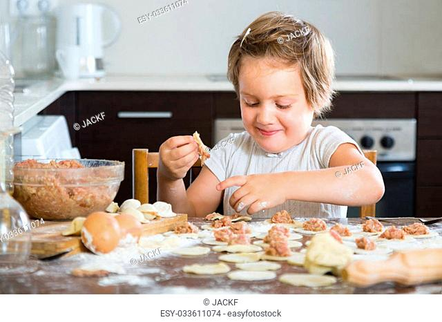 Happy little girl making fish dumplings from meat stuffing and dough at home kitchen