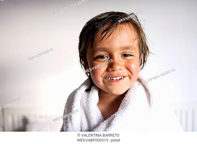 Portrait of smiling little boy with shower towel after taking a bath