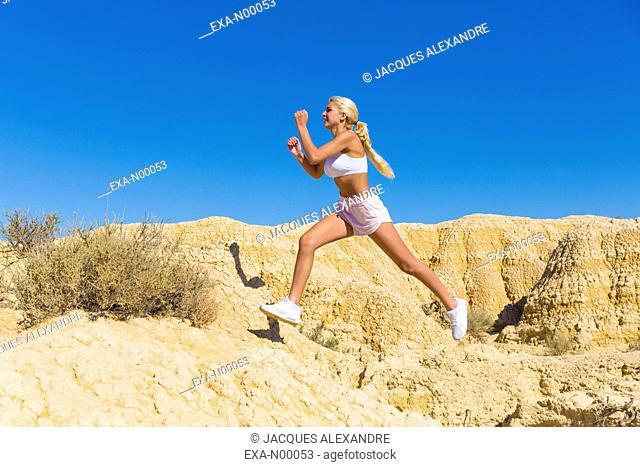 woman doing jogging, cross-country in deserted landscape in the Bardenas desert, Navarra, Spain