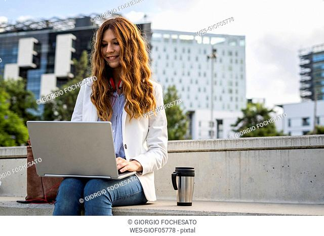 Young businesswoman sitting on stairs in the city, working with laptop
