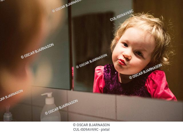 Over the shoulder view of girl wearing pink lipstick gazing at herself in mirror