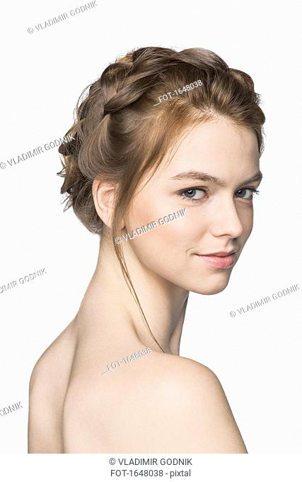 Portrait of shirtless beautiful woman smiling against white background