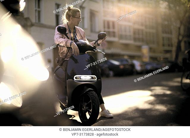 Woman on motor scooter, in Berlin, Germany