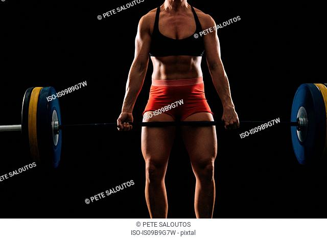 Mid section of young female weightlifter practicing barbell clean and jerk