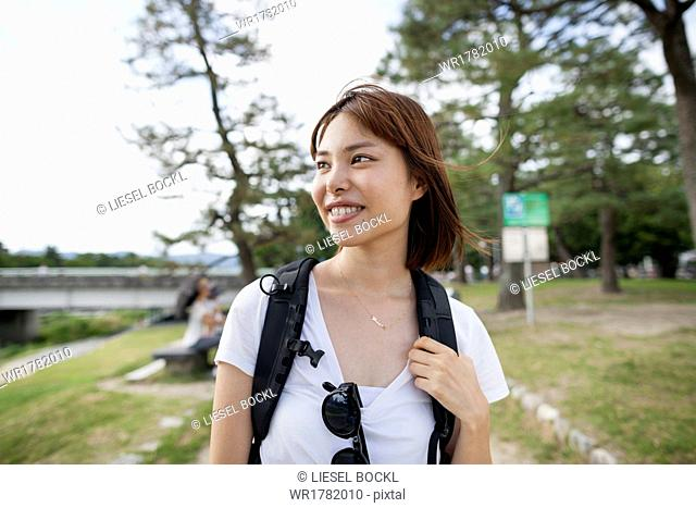 Young woman in the park carrying a rucksack