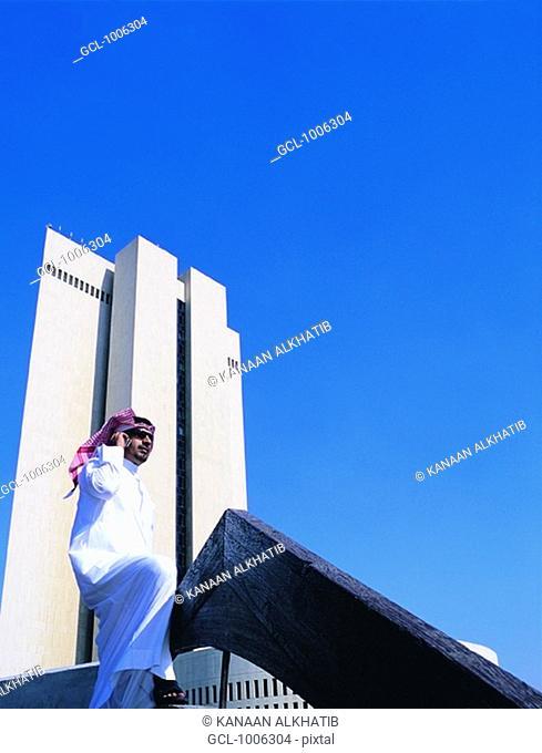 Saudi businessman using mobile phone in front of NCB building in Jeddah, Saudi Arabia