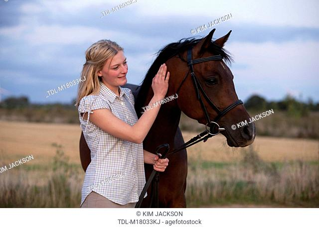 A young woman stroking an Arabian horse