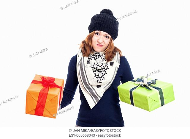 Disappointed woman in winter hat holding two presents, isolated on white background