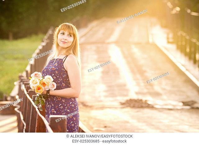 The charming young girl standing on a rustic bridge at dawn sun with a bouquet of roses
