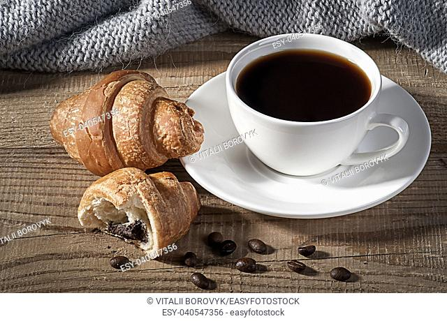 Black coffee with croissants. Coffee grains on a wooden table. Knitted woolen scarf in the background