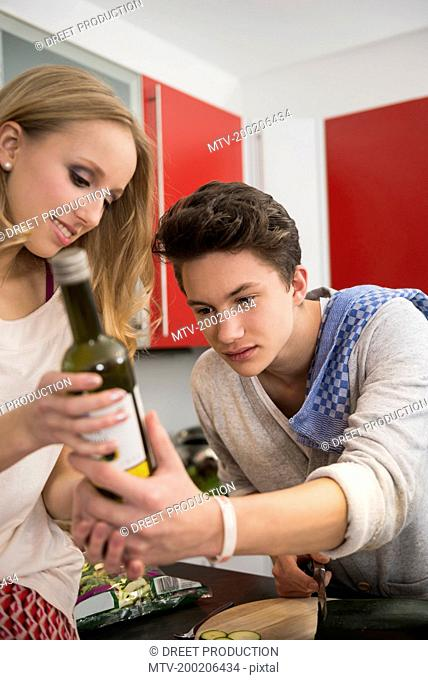 Young couple reading the label of a ingredient, Munich, Bavaria, Germany