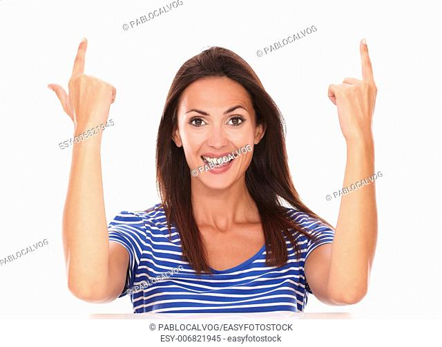 Smiling friendly lady with fingers pointing up gesturing a handgun in white background - copyspace