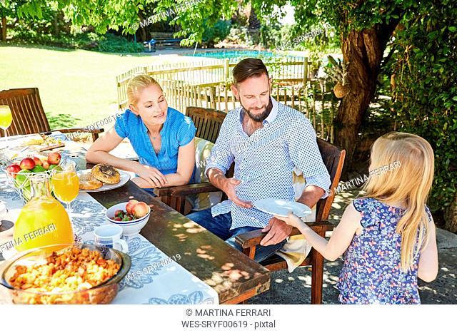 Girl serving plates for family at garden table