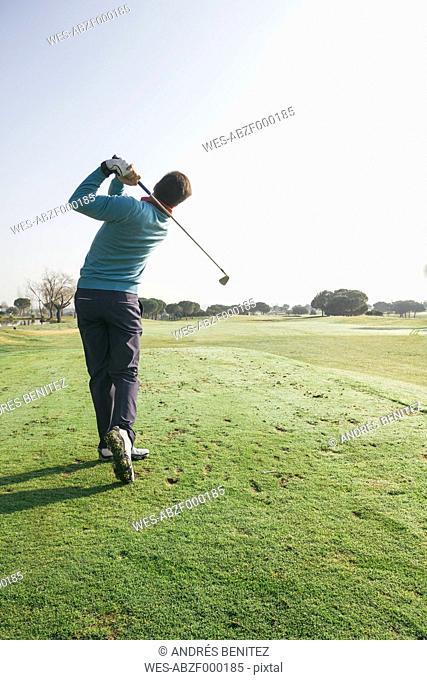 Golfer hitting a golf ball on a golf course