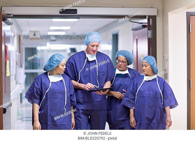 Surgeons using digital tablet in hospital hallway