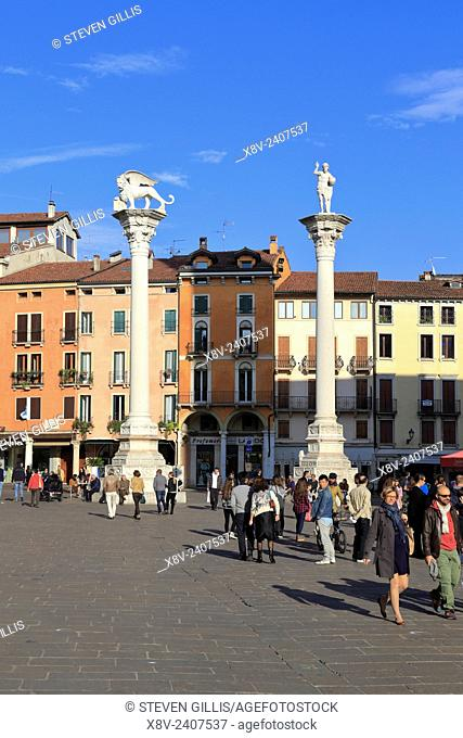 Tourists by the columns with the lion of St Mark and the Redeemer in Piazza dei Signori, Vicenza, Italy, Veneto