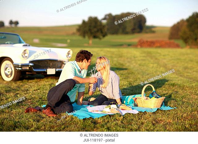 Couple Enjoying Countryside Picnic Next To Classic Car