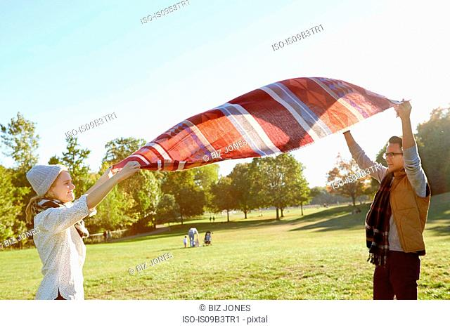 Couple shaking picnic blanket in park