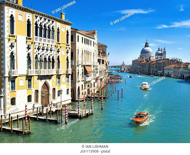 Water taxi boats on sunny Grand Canal in front of Santa Maria della Salute and architectural buildings in Venice, Italy