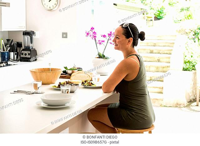 Woman sitting at kitchen island enjoying salad lunch