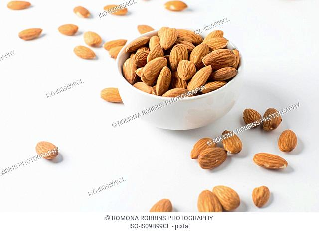 Almond nuts in bowl and on white background