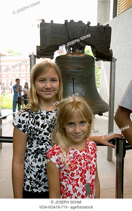 Two blond sisters stand in front of Liberty Bell, at Liberty Bell Center, in front of Independence Hall in historic area of Philadelphia, Pennsylvania