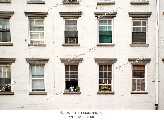A straight on facade view of an old apartment building in New York City showing rows of windows with religious statues on the sill of one window