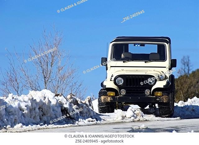 Jeep standing on snowy roadside on Pelion Peninsula, Thessaly, Greece