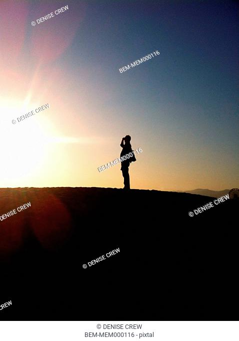 Silhouette of man on hill at sunset