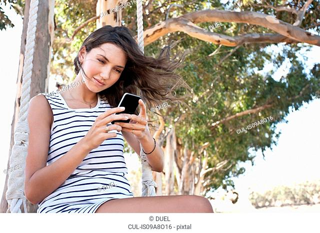 Young adult woman sitting on swing using smartphone