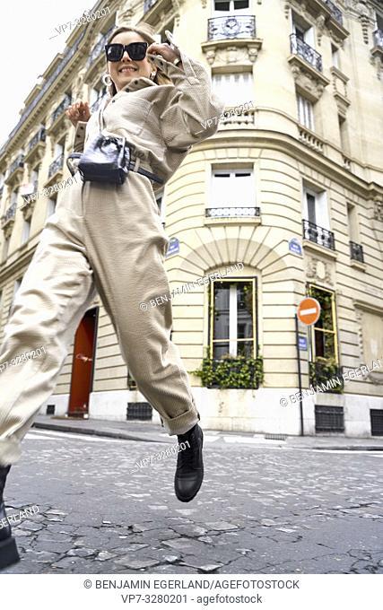 fashionable stylish woman running at street during fashion week, in Paris, France
