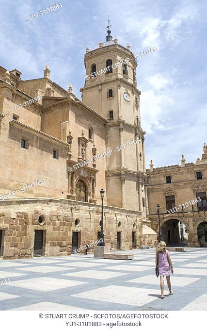 Female tourist walking in the by the colegiata de San Patricio church in the plaza de espana in Lorca Murcia Spain