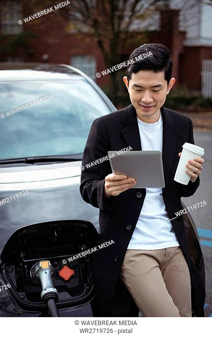 Man using digital tablet while charging car