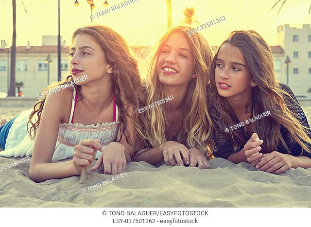 Best friends girls at sunset beach sand smiling happy together filtered image