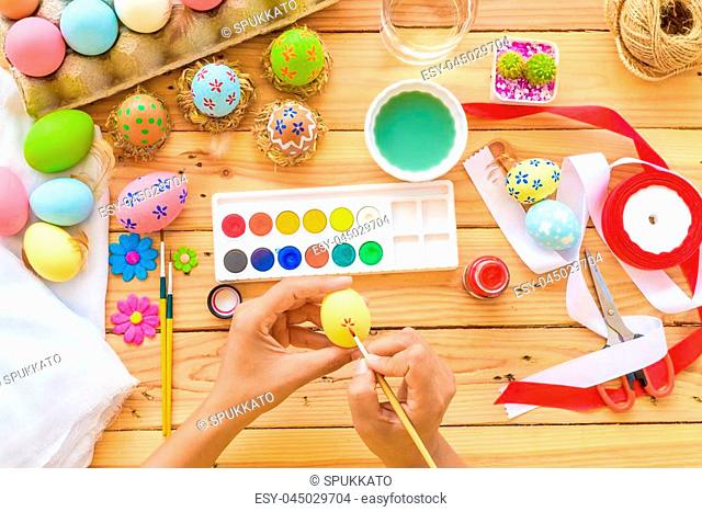 Happy easter! A woman hand painting Easter eggs. Happy family preparing for Easter