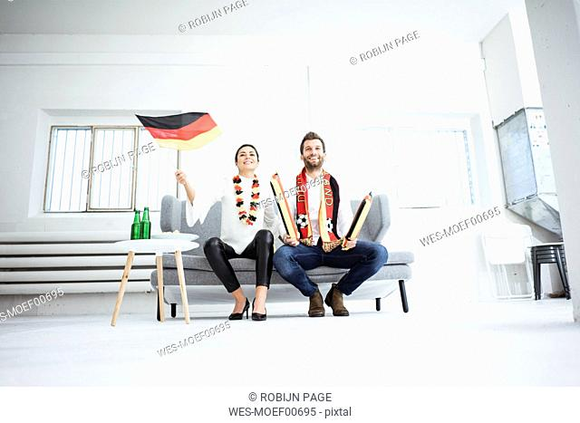Happy German football fan couple sitting on couch watching Tv