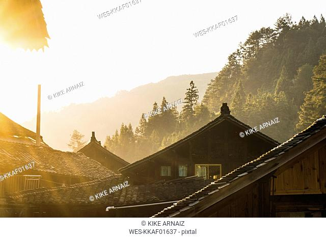 China, Guizhou, houses of a Miao settlement in backlight