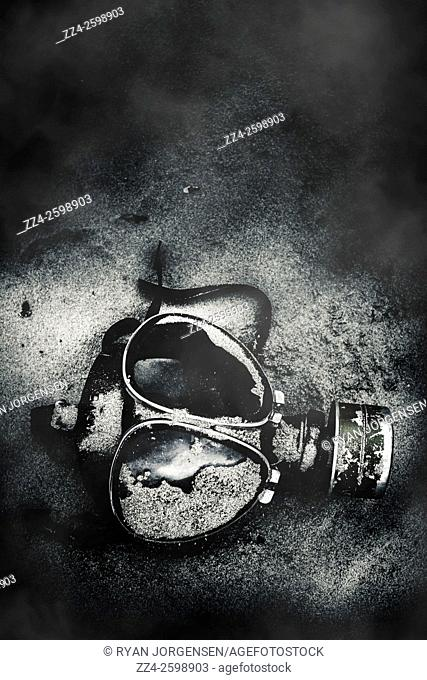 Atmospheric still life photo of a gasmask breathing apparatus abandoned on a hostile sand scene. Missing in action