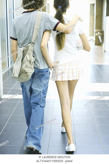 Teen couple walking in school hallway, rear view