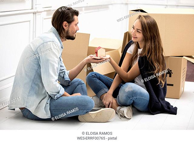 Man handing over tiny house model to girlfriend surrounded by cardboard boxes