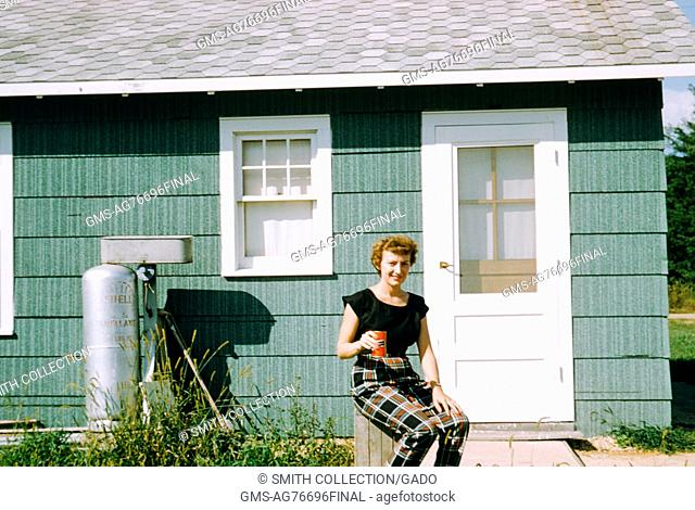 Red-haired woman sitting outside a mountain camping cabin and holding a can of soda, with Shell propane tank visible in the background, 1952