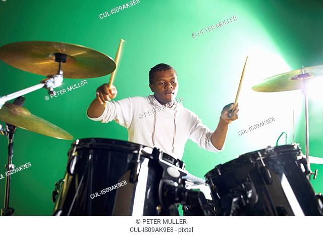 Male student playing drums in college music classroom