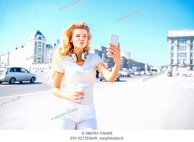 Beautiful young woman with music headphones and a take away coffee cup, taking selfie and making duck face against urban city background