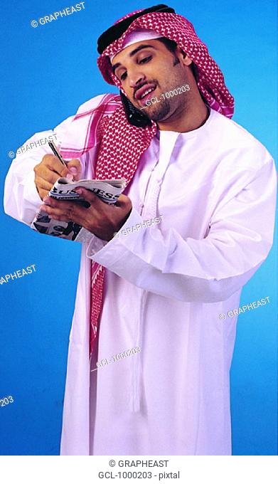 Arab businessman taking notes while on cell phone