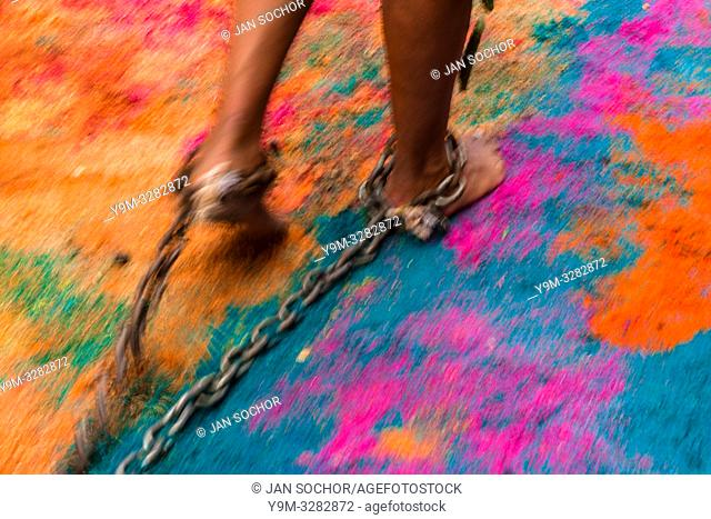A Catholic devotee, with cactus spines stuck to his leg, drags chains on a colorful sawdust carpet during the Holy week penitential procession in Atlixco