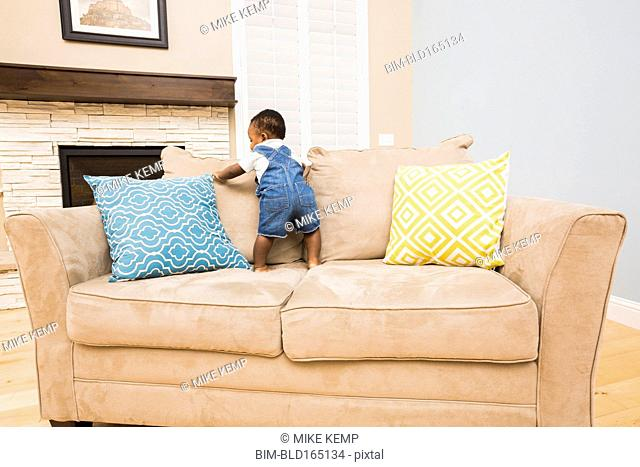 Black baby climbing on sofa in living room