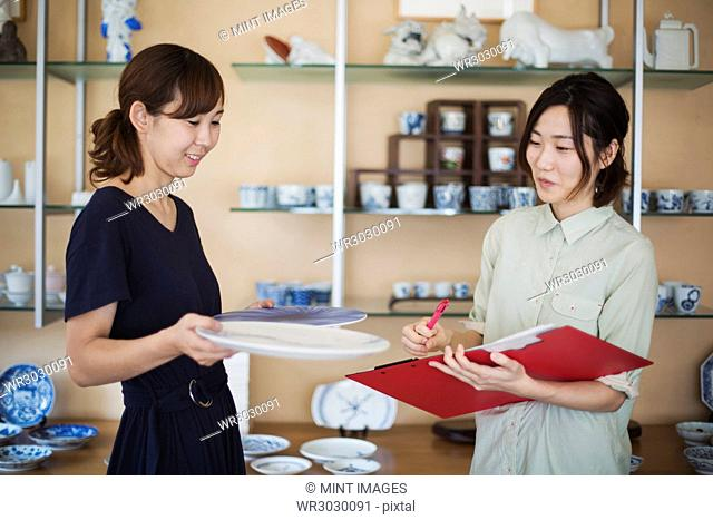 Two women standing in a Japanese porcelain shop, holding plates and document file